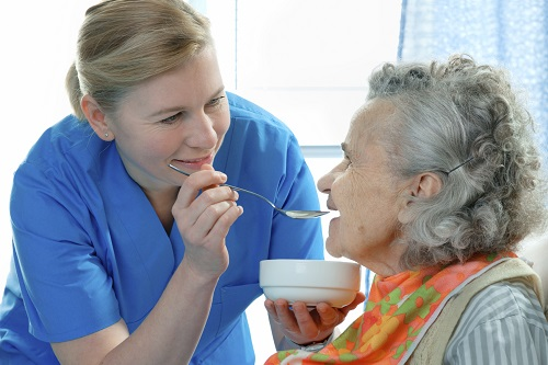 nursing student feeding resident in an aged care facility on placement